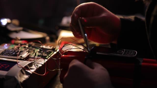 vídeos de stock e filmes b-roll de terrorist constructing a dynamite bomb in workshop - violência