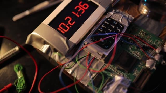 stockvideo's en b-roll-footage met terrorist de bouw van een tijdbom in de workshop alleen - bomb countdown timer