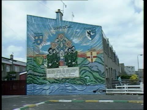 vídeos de stock e filmes b-roll de terrorist funds squeeze; terrorist funds squeeze; itn lib ext northern ireland: belfast mural showing masked ira men & 'ira - sinn fein' graffiti on... - bandido