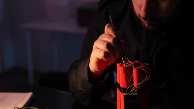 vídeos y material grabado en eventos de stock de terrorista haciendo una bomba de dinamita - haz de luz