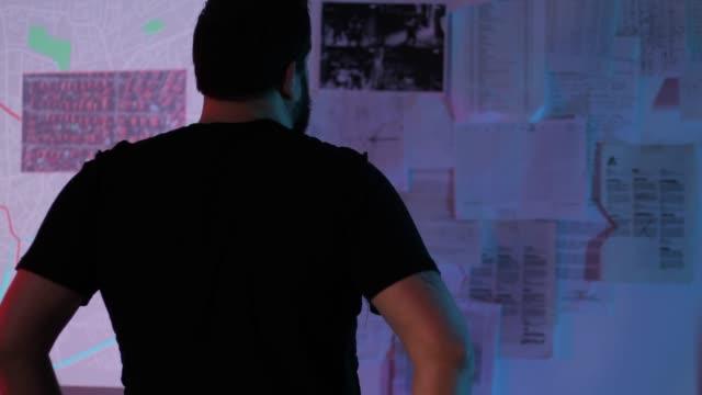 terrorist beobachtet stadtplan im dunklen raum - verbrecher stock-videos und b-roll-filmmaterial