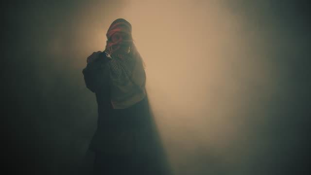 煙の背景で銃を振り回すテロリスト。 - 銃点の映像素材/bロール