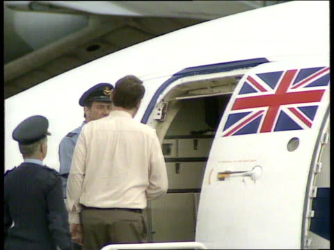 stockvideo's en b-roll-footage met raf akrotiri car on airbase tarmac carrying terry waite zoom in pan lr waite waves out of window ms waite waving at foot of plane steps and away to... - terry waite