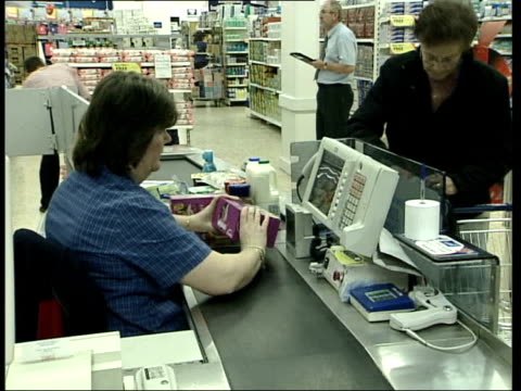 Britain's favourite supermarket ITN ENGLAND Hertfordshire Cheshunt INT Customers at tills of Tesco supermarket Checkout as items scanned thru LA...