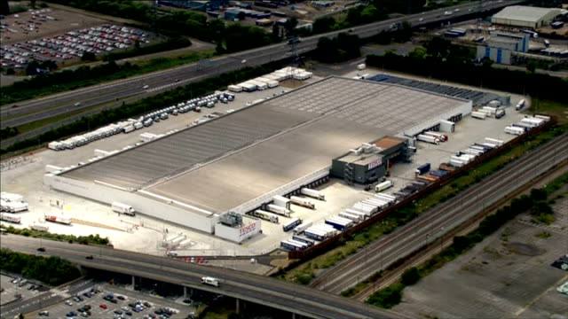 aerials england essex dagenham of tesco distribution warehouse building / lorries at loading stations / traffic along road next to warehouse /... - tesco点の映像素材/bロール