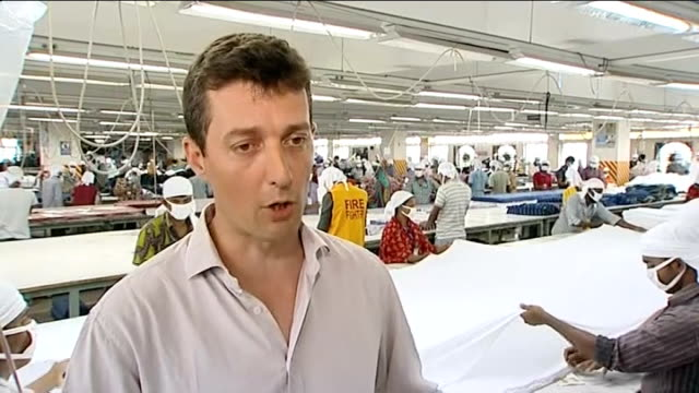 tesco pay factory workers double the country's minimum wage; bangladesh: dhaka: ext people towards guards watching people along legs stepping through... - garment stock videos & royalty-free footage