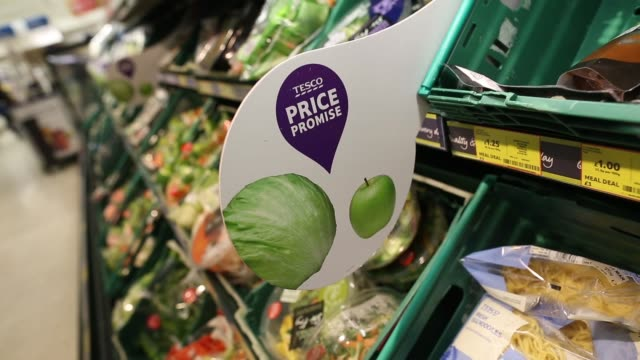 tesco price promise promotional signage in fresh vegetables section of a tesco plc supermarket in kensington west london shoppers pushing trolleys in... - 生鮮食品コーナー点の映像素材/bロール