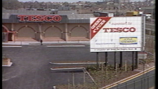 tesco profits fall for second year in a row location unknown ext new tesco supermarket workers working to finish new tesco supermarket empty shelves... - tesco点の映像素材/bロール