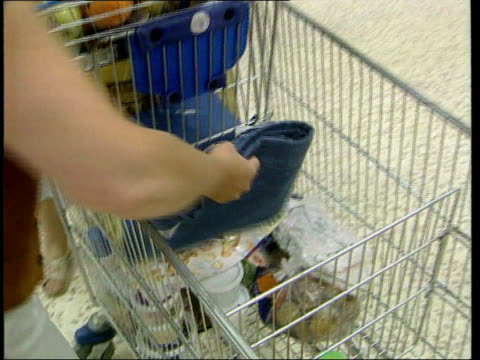 Tescos victory in grey market legal challenge LIB Shoppers taking pairs of Levi's jeans from table in Tesco supermarket Shoppers around table where...