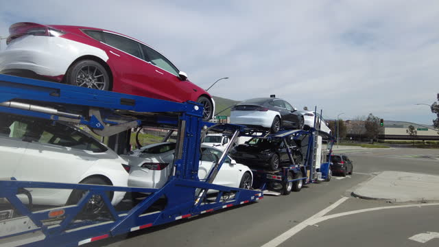 tesla cars are being transported on the highway in palo alto, california, on march 24, 2021. - large group of objects stock videos & royalty-free footage