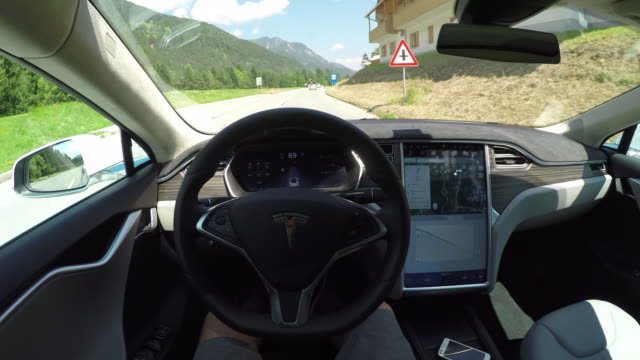 fpv: tesla electric car self driving and turning on local road. autonomous vehicle driving without a driver - land vehicle stock videos & royalty-free footage