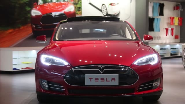 a tesla motors inc model s electric vehicle stands on display near the entrance of the company's showroom in beijing china on tuesday nov 11 tesla... - general motors stock videos & royalty-free footage