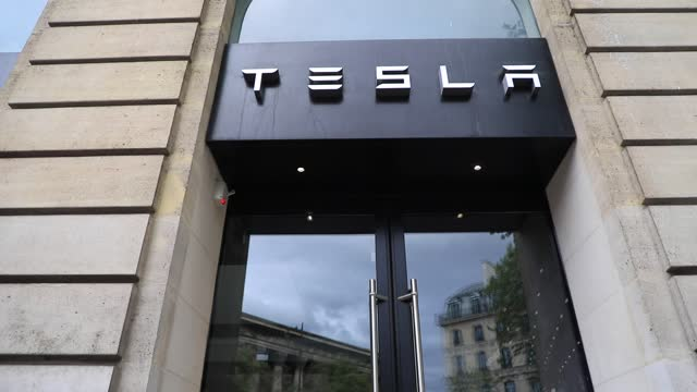 tesla sign is on display on may 4, 2021 in paris, france. in france, the american firm tesla has been deploying its fast charging stations all over... - logo stock videos & royalty-free footage