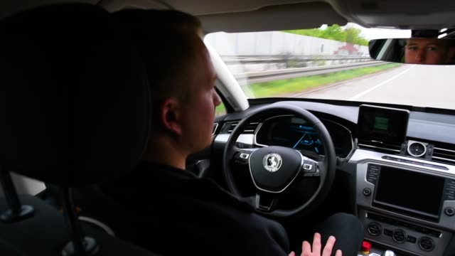 test driver rests his hands as artificial intelligence takes over driving the car during tests of autonomous car abilities conducted by continental... - personal land vehicle stock videos & royalty-free footage