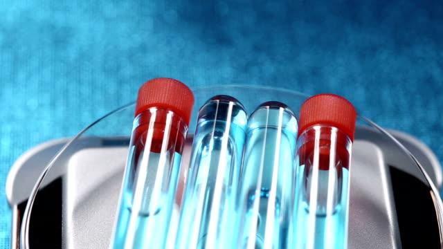 test tube mit roter mütze, innen ist blau flüssigen probe in gllass poly, rotierenden kreis auf gerät maching, blauer hintergrund - hergestellter gegenstand stock-videos und b-roll-filmmaterial