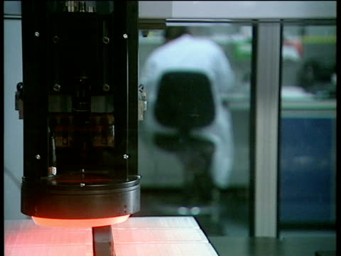 DNA testing equipment in action back of seated scientist in white coat in background