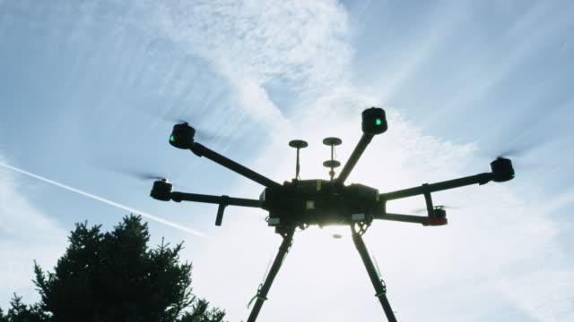 eine tethered hexacopter drohne steigt in einen hellblauen himmel - abheben aktivität stock-videos und b-roll-filmmaterial