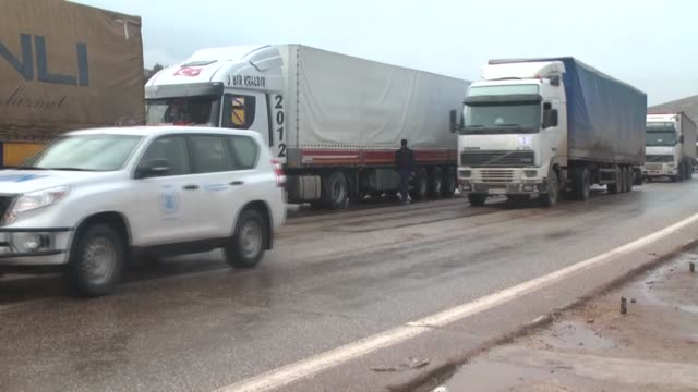tewntyone united nations trucks carrying food medicine and other aid supplies crossed through the turkish border gate of cilvegozu in hatay heading... - convoy trucks stock videos and b-roll footage