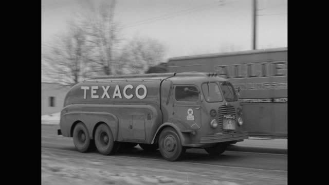ws pan texaco tank truck passing another truck on road in winter / united states - western script stock videos & royalty-free footage
