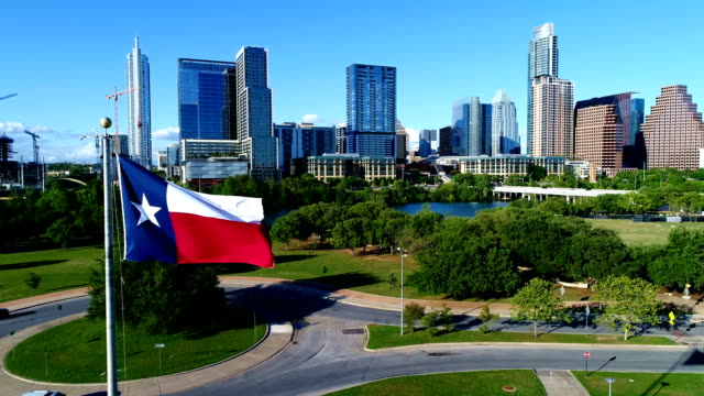 vídeos de stock e filmes b-roll de texas flag on perfect flag pole in front of perfect austin skyline - texas