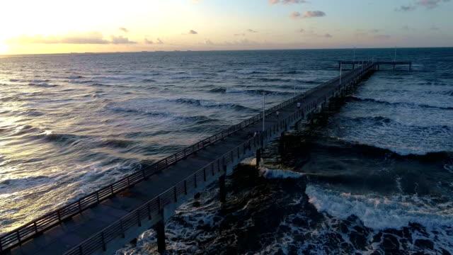 texas gulf coast backing up over port aransas pier , on padre island , texas , usa amazing gorgeous sunrise over gulf of mexico long pier - corpus christi texas stock videos & royalty-free footage