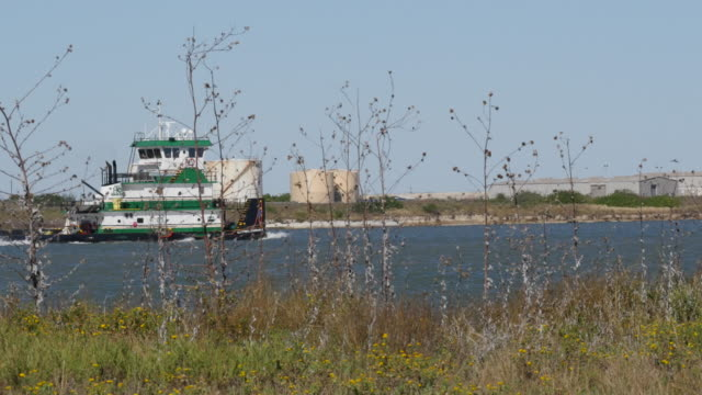 texas gulf coast work boat passes oil tanks - fuel storage tank stock videos and b-roll footage
