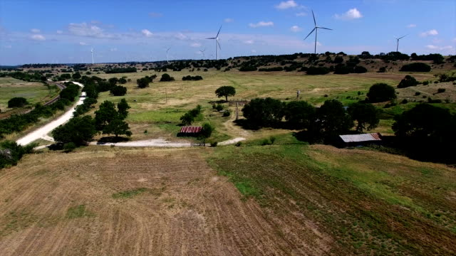 Texas hill Country farm with Wind Turbines on the hilltop in the background