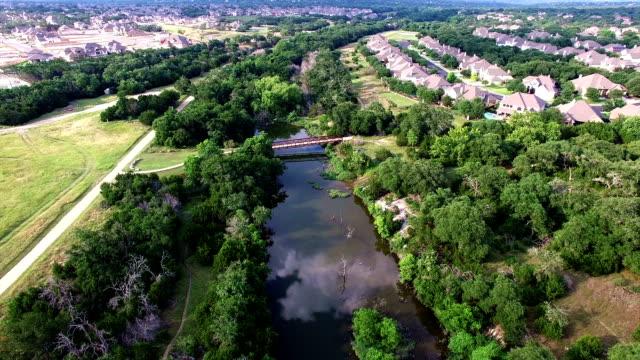 中央テキサスのテキサスの丘の国郊外ゴルフ コース、クリーク空中ビュー - 木を抱く点の映像素材/bロール