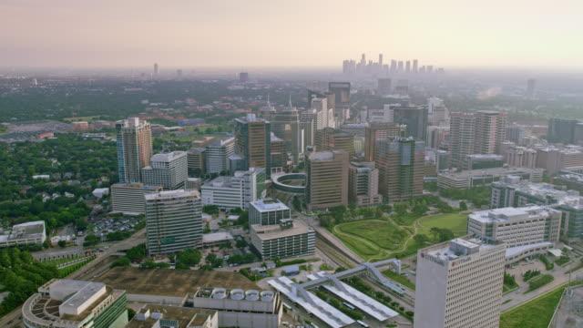 vídeos de stock e filmes b-roll de aerial texas medical center with downtown houston in the background - edifício médico