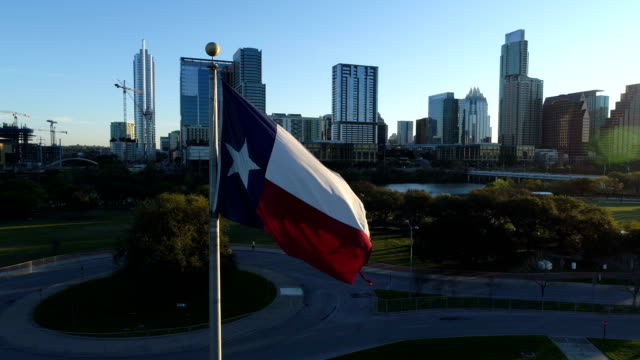 texas state flag pan right aerial drone view close to flag during sunrise over austin texas skyline cityscape of capital cities - austin texas video stock e b–roll
