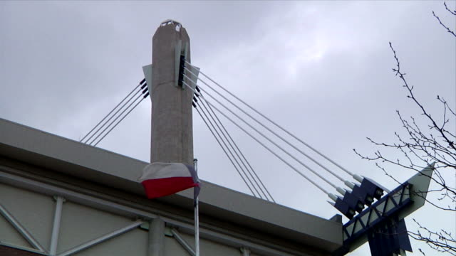 Texas state flag waving in wind near Alamodome Stadium roof roof support mast under overcast sky