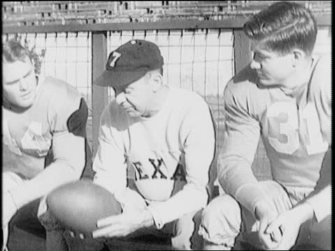 texas university players pete layden in letterman jacket and jack crain in cowboy hat pose with a texan flag flying between them / crain reads a book... - letterman stock videos & royalty-free footage