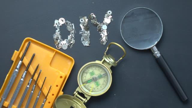 vidéos et rushes de bricolage de texte écrit avec clockworks, compas, outils de travail et loupe sur tableau noir - selimaksan