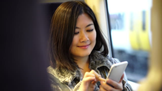 Text message on a train, attractive Asian woman. 1