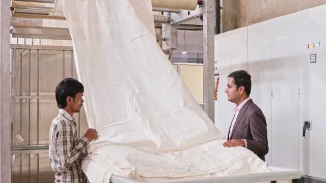 textile factory owner checking raw textile with production line worker - textile stock videos & royalty-free footage
