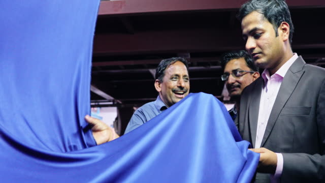 textile factory owner checking the quality of silk production with his team - textile stock videos & royalty-free footage