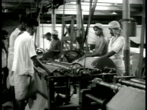 textile mill w/ indian workers manning machines looms making cloth indian women working thread machines spools wwii world war ii colonial india... - 織物工場点の映像素材/bロール