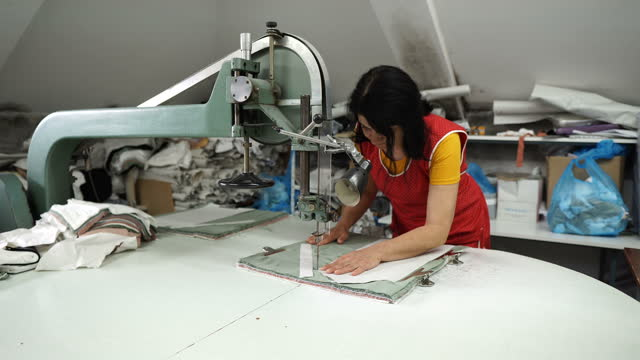 textile worker cuts a tough fabric with a  cutter. sewing factory - needle plant part stock videos & royalty-free footage