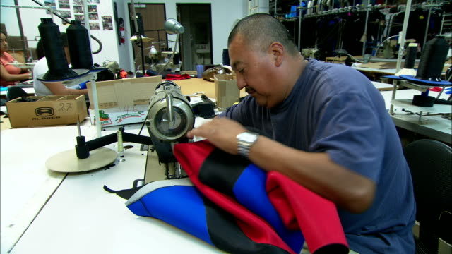 stockvideo's en b-roll-footage met textile workers sew pieces of neoprene-backed cloth into garments. - kledingstuk