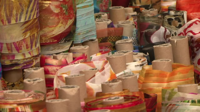 textiles and fabrics. handheld pan-left across rolls of colorful fabric ending on a giant red pair of scissors. - textile stock videos & royalty-free footage