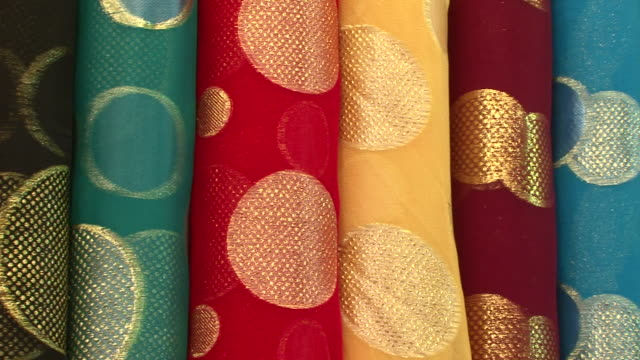 textiles and fabrics. pan-right on colorful silk satin rolls of fabric embroidered with circles of gold thread. - textile stock videos & royalty-free footage