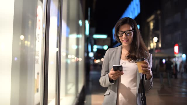 texting and windowshopping downtown at night - window display stock videos & royalty-free footage