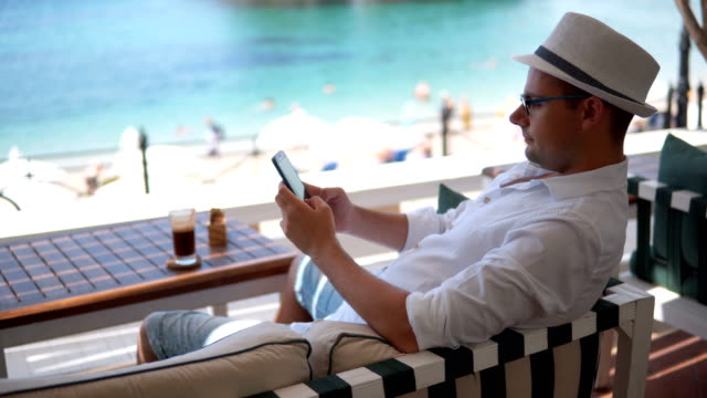 texting in sea side cafe - wireless technology stock videos & royalty-free footage