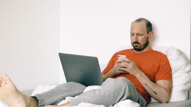 ベッドでリラックスしながらスマートフォンでテキストメッセージ - 落ち着かない点の映像素材/bロール