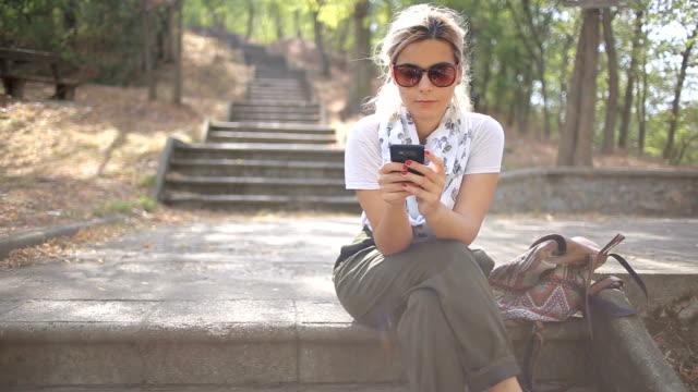 vídeos de stock, filmes e b-roll de mensagem de texto em escadas - mulher bonita