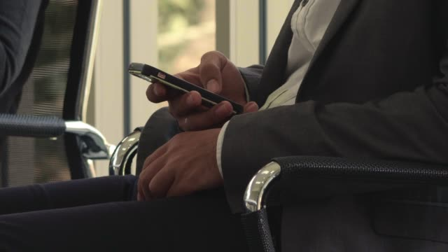 Texting with cell phone in conference room meeting