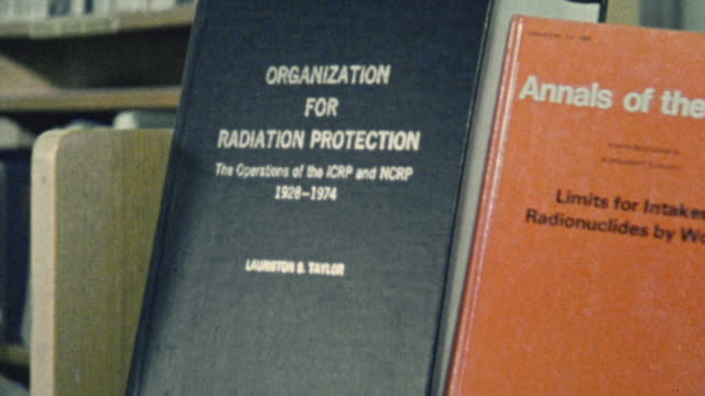 1983 montage texts about radiation in a library setting / united kingdom - textbook stock videos & royalty-free footage