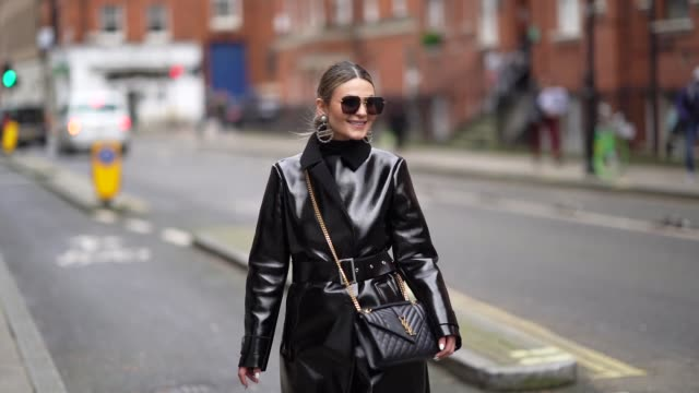 tezza wears sunglasses, chanel earrings, a black shiny leather long coat, a belt, a chanel quilted bag, leggings, black leather pointy shoes, during... - leggings stock videos & royalty-free footage