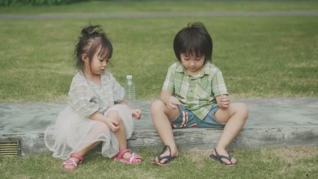 thailändska barn sitter i trädgården och prata för avkoppling - 4 5 år bildbanksvideor och videomaterial från bakom kulisserna