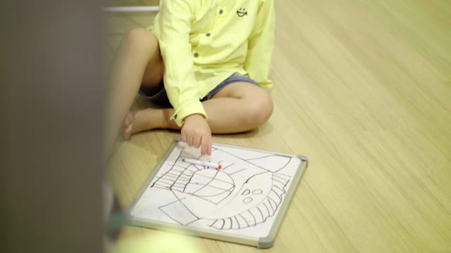 Thai baby boy is sketching and drawing on notepad for practice and relaxation